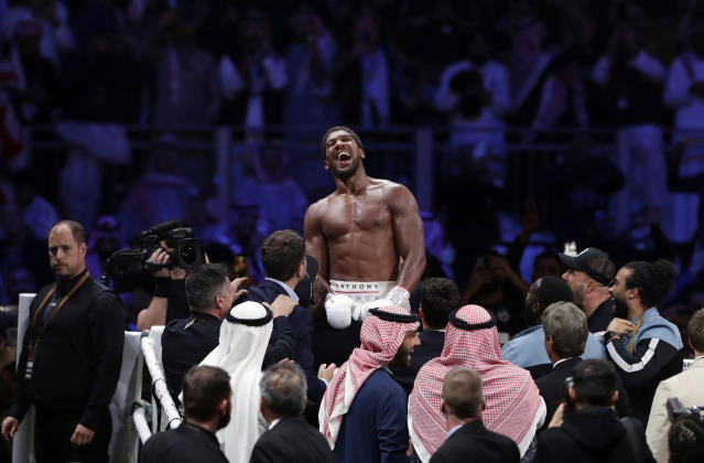 FILE - In this Sunday, Dec. 8, 2020 file photo, Britain's Anthony Joshua celebrates after beating Andy Ruiz Jr. to win their World Heavyweight Championship contest at the Diriyah Arena, Riyadh, Saudi Arabia. Joshuas first fight as the restored world heavyweight champion could take place in front of no fans. British boxings governing body has told promoters it hopes to be able to have shows back from July, 2020 after months of inactivity because of the coronavirus outbreak. (AP Photo/Hassan Ammar, File)