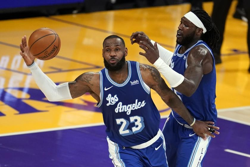 Los Angeles Lakers forward LeBron James (23) grabs a rebound next to center Montrezl Harrell during the second half of the team's NBA basketball game against the Denver Nuggets on Thursday, Feb. 4, 2021, in Los Angeles. (AP Photo/Marcio Jose Sanchez)