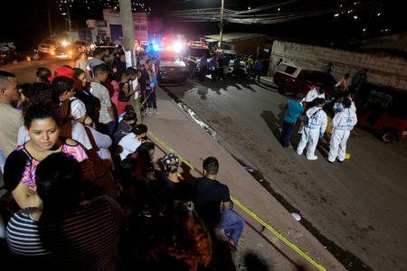 FILE PHOTO: Onlookers chat as members of a forensic team work at a crime scene where gunmen killed five people at a working class neighbourhood in Tegucigalpa