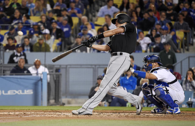 Miami Marlins' J.T. Realmuto hits a solo home run as Los Angeles Dodgers catcher Austin Barnes watches during the third inning of a baseball game Tuesday, April 24, 2018, in Los Angeles. (AP Photo/Mark J. Terrill)