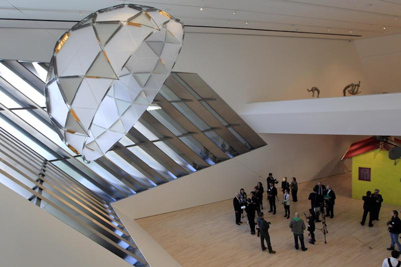 "In this Nov. 9, 2012 photo members of the media tour the Eli and Edythe Broad Art Museum on Michigan State University's campus in East Lansing, Mich. The canopy sculpture seen at upper left is ""Red Factor"" by Inigo Manglano-Ovalie. (AP Photo/Carlos Osorio)"