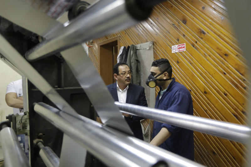 "In this Monday, March 3, 2014 photo, Adel Abd ElSadk, left, owner of the pharmaceutical packaging company Trustpack, talks with an employee manning one of the machines at his factory which has been financed in part by loans from the Social Development Fund, located just outside Cairo, Egypt. The program, called ""The Project"" in Arabic, highlights entrepreneurship and small business acumen - something experts say is more crucial than ever as Egypt tries to claw its way out of tough economic times. (AP Photo/Amr Nabil)"