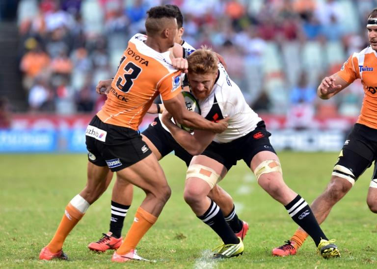 Sunwolves' Ed Quirk (C) fights for the ball with Cheetahs' Ryno Benjamin during their Super Rugby match, at the Bloemfontein stadium in Bloemfontein, South Africa, on March 11, 2017