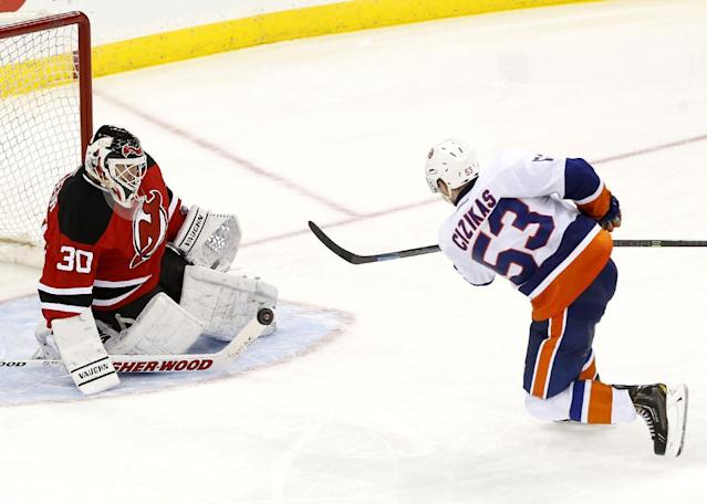 New Jersey Devils goalie Martin Brodeur (30) blocks a shot by New York Islanders center Casey Cizikas (53) during the third period of an NHL hockey game on Friday, April 11, 2014, in Newark, N.J. The Islanders won 3-2. (AP Photo/Julio Cortez)