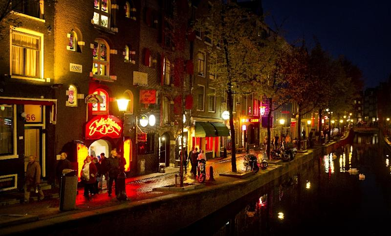 People walk through the red-light district, known as De Wallen, in Amsterdam, on October 13, 2011