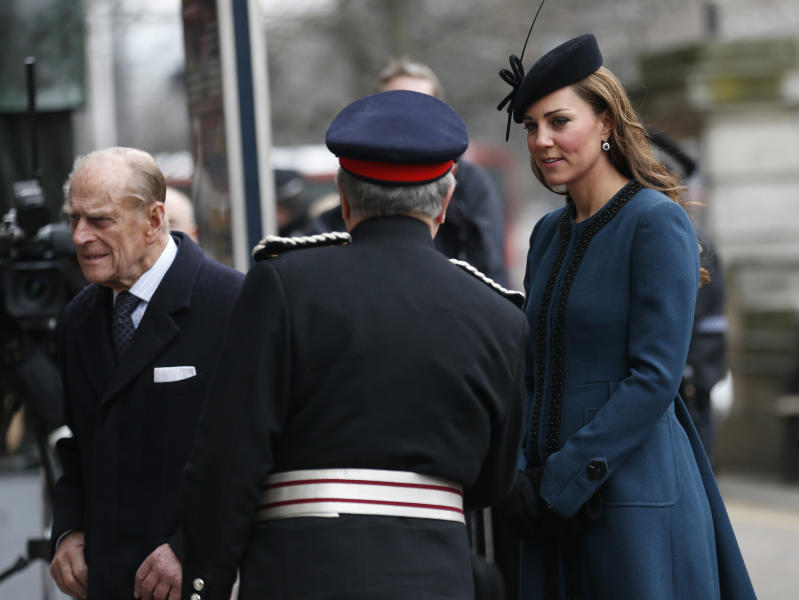 Britain's Kate, Duchess of Cambridge, right, accompanies Queen Elizabeth II, unseen, and Prince Philip, left, at Baker Street underground station in London for a visit to mark the 150th anniversary of the London Underground, Wednesday, March 20, 2013. (AP Photo/Sang Tan)
