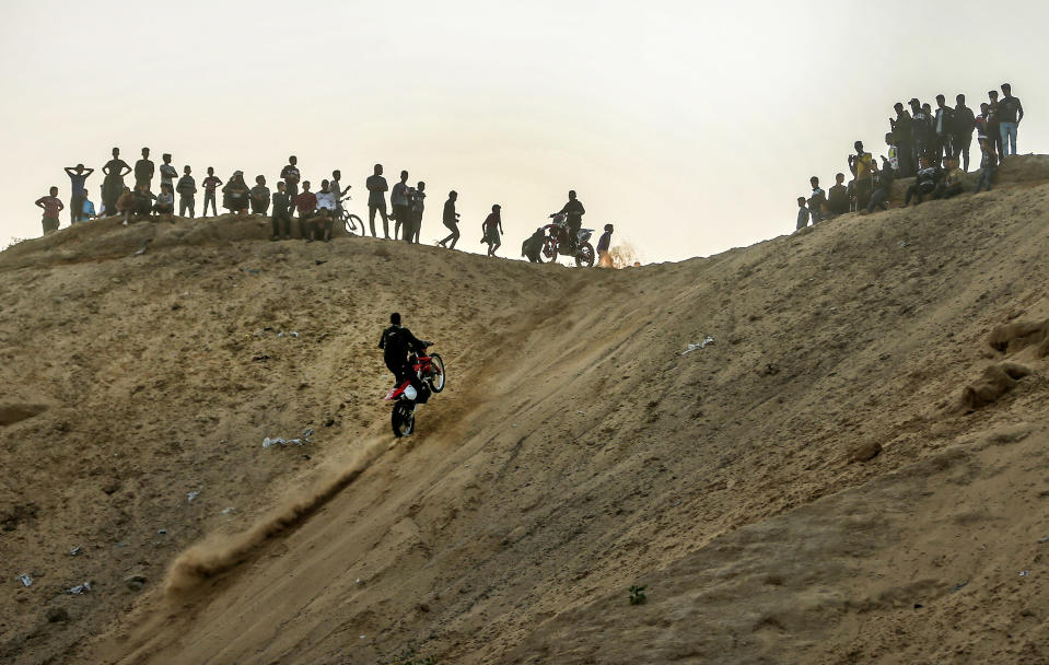Spectators watch as a young Palestinian rides his motorcycle up a sandy hill during a weekly show in the Al-Zahra area, near Gaza