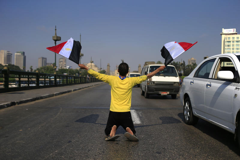 A man waves Egyptian flags as he kneels on a bridge that leads to Tahrir Square in Cairo, Egypt, Friday, July 26, 2013. Political allies of Egypt's military lined up behind its call for huge rallies Friday to show support for the country's top general, pushing toward a collision with Islamist opponents demanding the return of Mohammed Morsi, the nation's ousted president. (AP Photo/Hassan Ammar)