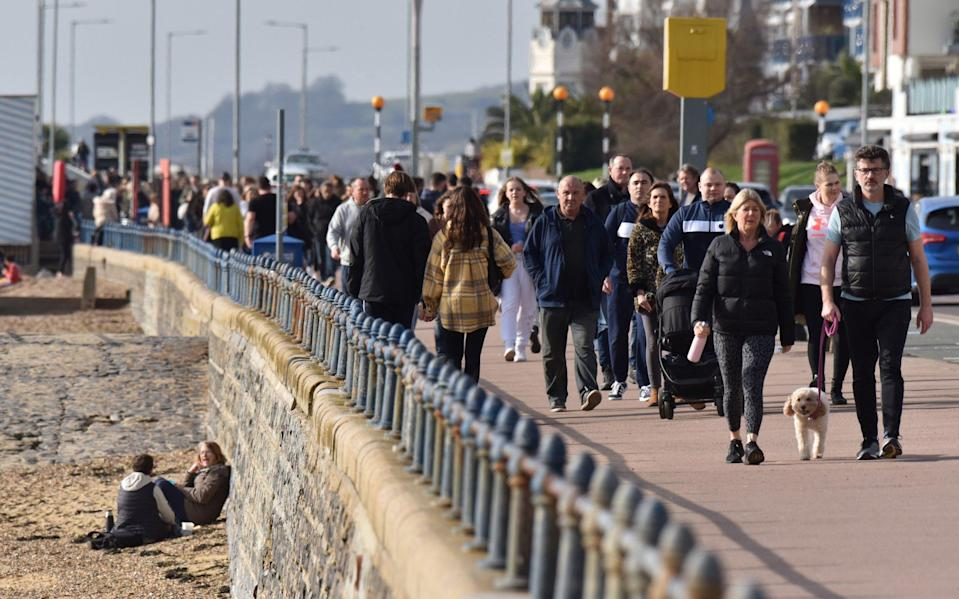 People walk beside the beach on a warm sunny day as the weather warms for the week ahead on February 21, 2021 in Southend,