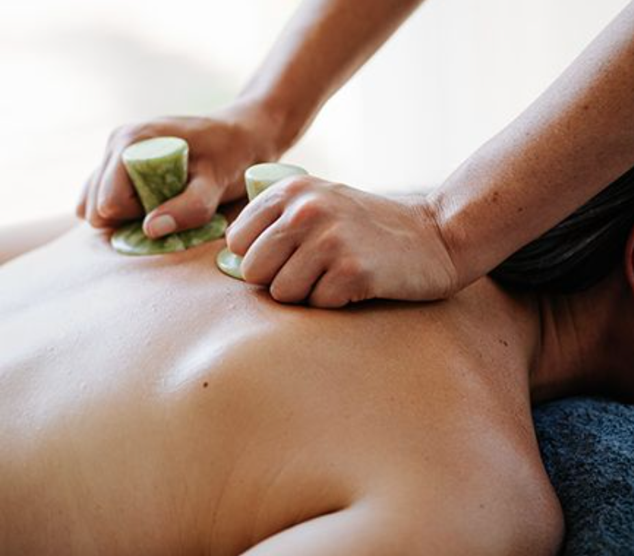 woman getting massaged with jade stones