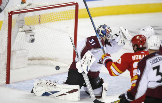 Calgary Flames center Sean Monahan (23) scores on Colorado Avalanche goaltender Philipp Grubauer (31) during the third period of Game 2 of an NHL hockey first-round playoff series Saturday, April 13, 2019, in Calgary, Alberta. (Jeff McIntosh/The Canadian Press via AP)