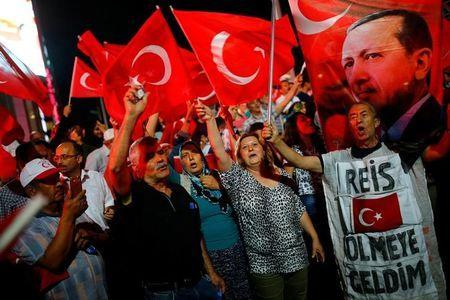 """People shout slogans and wave Turkish national flags as they have gathered in solidarity night after night since the July 15 coup attempt in central Ankara, Turkey, July 27, 2016. The banner on the right reads """"Chief (Erdogan) I came to die"""". REUTERS/Umit Bektas"""