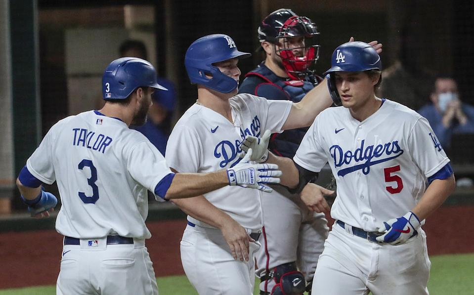 Dodgers shortstop Corey Seager is congratulated by Joc Pederson and Chris Taylor after hitting a three-run home run