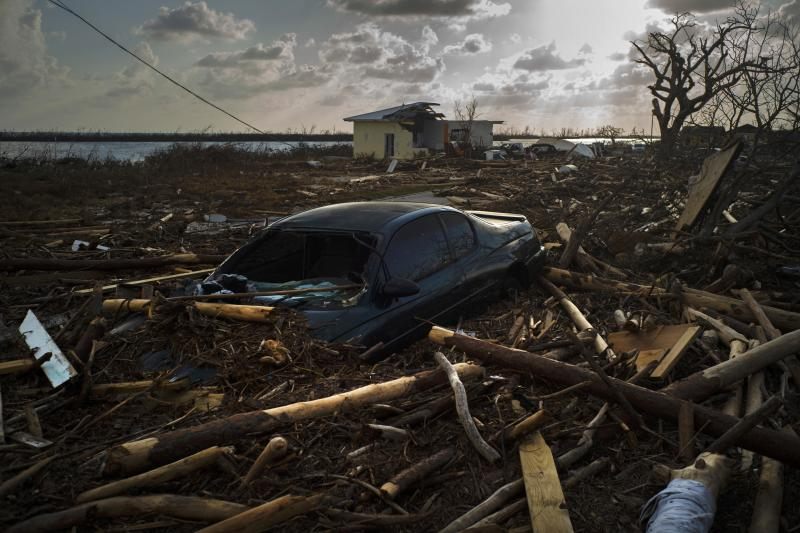 A car is sunk in the wreckage and debris caused by Hurricane Dorian, in Mclean's Town, Grand Bahama, Bahamas, Wednesday Sept. 11, 2019. Bahamians are tackling a massive clean-up a week after Hurricane Dorian devastated the archipelago's northern islands. Residents sift through debris as they try to save prized possessions and prepare to rebuild from one of the strongest Atlantic hurricanes in history. (AP Photo/Ramon Espinosa)