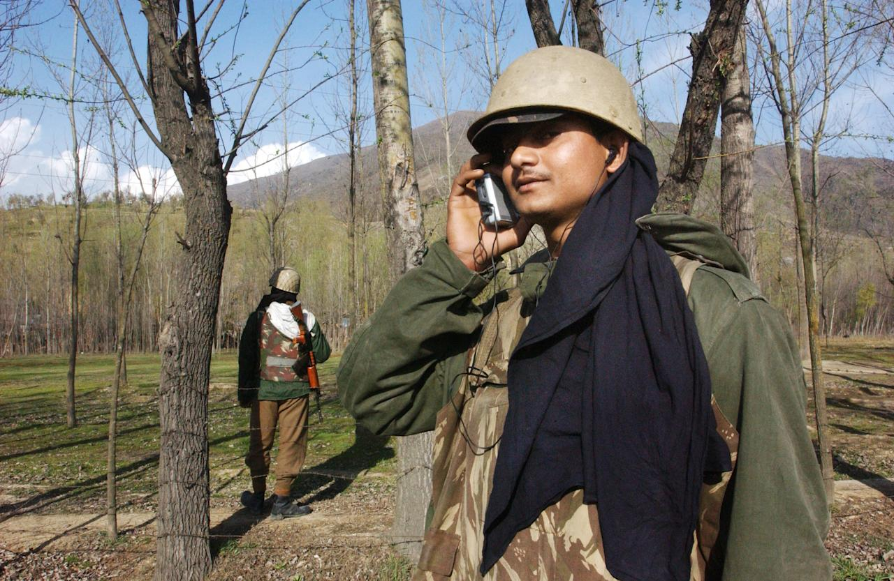 SRINAGAR, KASHMIR, INDIA - MARCH 13: Indian Border Security Force soldiers listen to the Indian cricket team play Pakistan in the first one-day international cricket match held in Karachi, Pakistan, March 13, 2004 at their camp in Srinagar, India. This is the first cricket tour held in Pakistan between the two nations in 14 years.  (Photo by Ami Vitale/Getty Images)