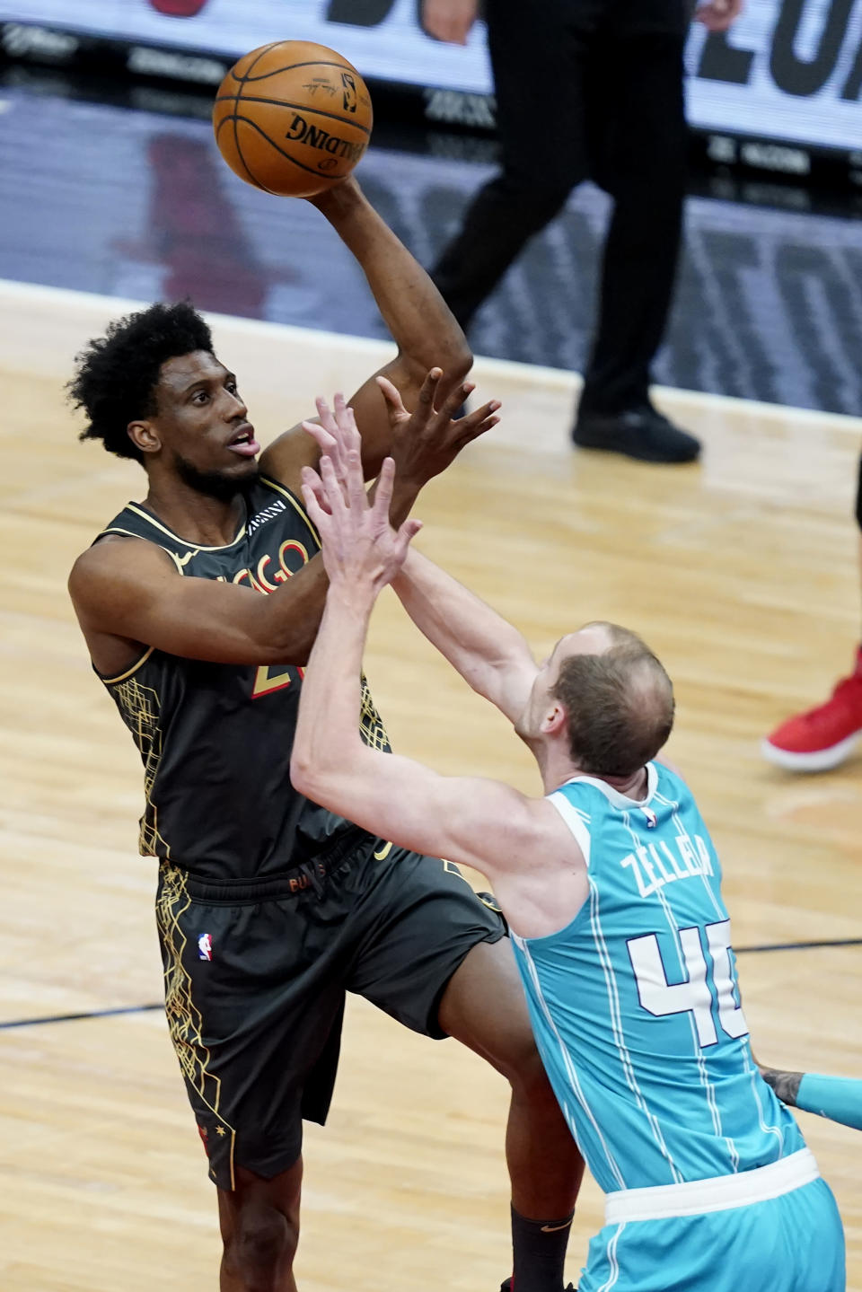 Chicago Bulls' Thaddeus Young, left, shoots over Charlotte Hornets' Cody Zeller during the first half of an NBA basketball game Thursday, April 22, 2021, in Chicago. (AP Photo/Charles Rex Arbogast)