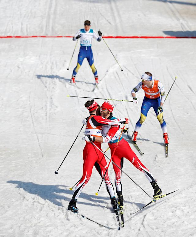 Cross-Country Skiing - Pyeongchang 2018 Winter Paralympics - Men's 1.5km Sprint Classic - Visually Impaired - Final - Alpensia Biathlon Centre - Pyeongchang, South Korea - March 14, 2018 - Brian Mckeever (182) of Canada celebrates winning gold with his guide Russell Kennedy. REUTERS/Carl Recine