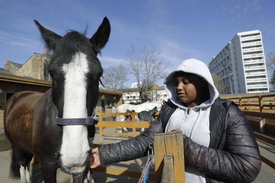 Zion Mcleod, 13, strokes Eddie at Ebony Horse Club in Brixton, south London, Sunday, April 18, 2021. In the midst of south London's hustle and bustle, only a 10-minute walk from a subway station, is a school where children are encouraged to horse around. The Ebony Horse Club provides 140 rides per week to children in the local community offering them the opportunity to learn important life skills along with horseback riding. (AP Photo/Kirsty Wigglesworth)