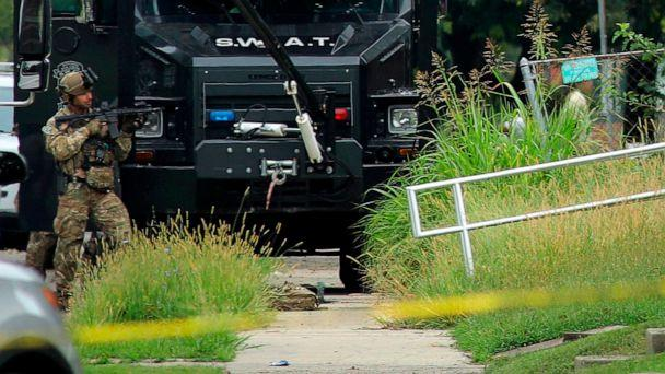 PHOTO: A police officer in tactical gear stands positioned near an Illinois State Police SWAT vehicle outside a building on 42nd Street near Van Buren Avenue, on Friday, Aug 23, 2019, in East St. Louis, Ill., after a trooper was shot serving a warrant. (Christian Gooden/St. Louis Post-Dispatch via AP)