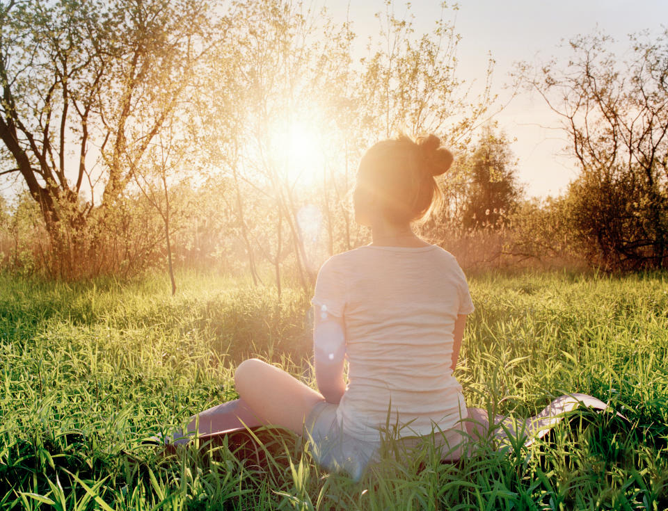 Young woman sitting in yoga position enjoying sunset in nature
