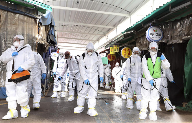 "Workers wearing protective suits spray disinfectant as a precaution against the coronavirus at a market in Bupyeong, South Korea, Monday, Feb. 24, 2020. South Korea reported another large jump in new virus cases Monday a day after the the president called for ""unprecedented, powerful"" steps to combat the outbreak that is increasingly confounding attempts to stop the spread. (Lee Jong-chul/Newsis via AP)"