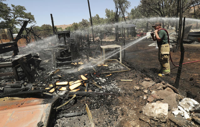 <p>A Green River firefighter cleans up after a brush fire near Pack Creek in Moab, Utah, Wednesday, June 13, 2018. A fast-moving brush fire destroyed homes in the Utah tourist town of Moab, while several thousand people in Colorado and Wyoming fled multiple wildfires scorching the drought-stricken U.S. West on Wednesday. (Photo: Jeffrey D. Allred/The Deseret News via AP) </p>