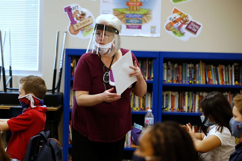 A teacher wears a face shield while handing out papers to students at a public charter school in Utah this week. Source: Getty