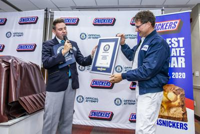 Guinness World Record adjudicator Michael Empric presents a title certificate to Mars Wrigley representative Ruud Engbers for the largest chocolate nut bar ever created Thursday, Jan. 16, 2020, in Waco, Texas. The more than two tons SNICKERS bar was made using a 1200 pound combination of caramel, nougat and peanuts, and 3500 pounds of chocolate. (Drew Anthony Smith/AP Images for SNICKERS)