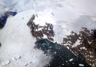 FILE - In this file photo dated Thursday, Aug. 3, 2017, a glacier at left calves icebergs into a fjord off the Greenland ice sheet in southeastern Greenland. The Danish Meteorological Institute said Sunday June 16, 2019, the melting season in Greenland has started a month earlier than usual, and issued a photo by climate researcher Rasmus Tonboe on Twitter showing what they say are sled dogs dragging a sleigh on the ice in Greenland with their paws in melted ice water.(AP Photo/David Goldman, FILE)