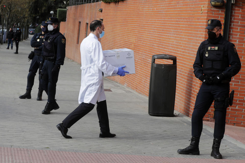 Police stand by the entrance of a nursing home as a box of some of the first Pfizer coronavirus vaccines arrives in Madrid, Spain, Sunday Dec. 27. 2020. Spain plans to receive over 4.5 million doses of the vaccine over the next three months, enough it says to immunize just over 2.2 million people. The government estimates that this first phase will be enough to cover nursing home residents and workers, followed by health workers in general and people with disabilities. (AP Photo/Paul White)