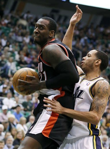Portland Trail Blazers forward J.J. Hickson, left, is defended by Utah Jazz guard Devin Harris during the first half of an NBA basketball game, Thursday, April 26, 2012, in Salt Lake City. (AP Photo/Jim Urquhart)