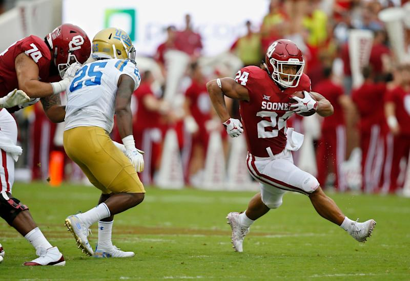 Oklahoma running back Rodney Anderson (24) runs around UCLA linebacker Tyree Thompson (25) in the first half of an NCAA college football game in Norman, Okla., Saturday, Sept. 8, 2018. (AP Photo/Sue Ogrocki)