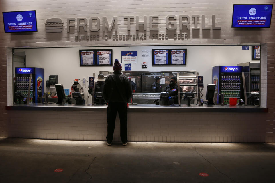 A fan looks at the menu at a concession stand as teams warm up before an NFL wild-card playoff football game between the Buffalo Bills and the Indianapolis Colts at Bills Stadium Saturday, Jan. 9, 2021, in Orchard Park, N.Y. (AP Photo/Jeffrey T. Barnes)