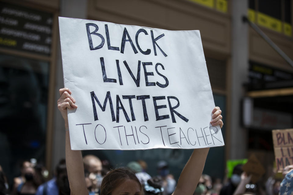 """A white protester in Times Square holds a handmade sign that reads, """"Black Lives Matter To This Teacher"""".  (Photo by Ira L. Black/Corbis via Getty Images)"""