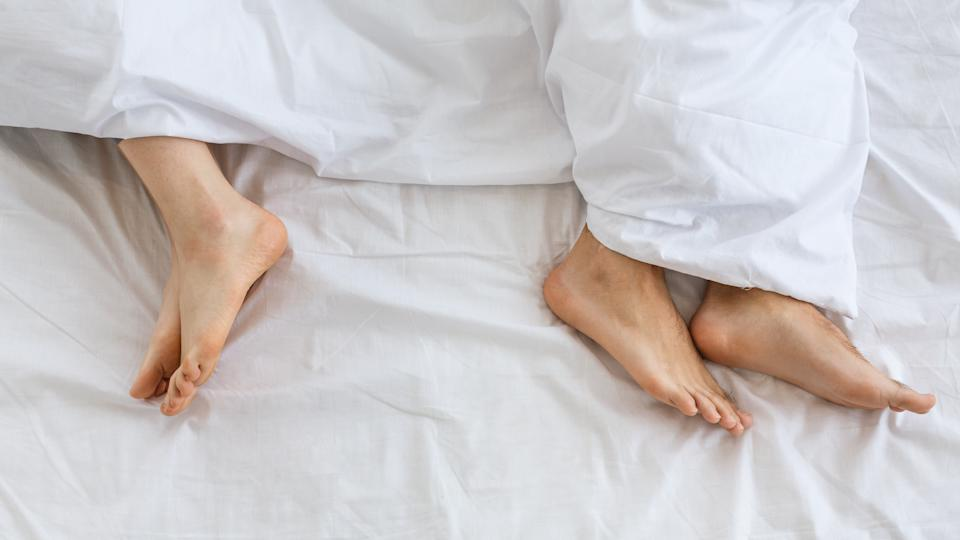 Problems in family relationship. Feet of man and woman in white bed at distance, top view, panorama, free space