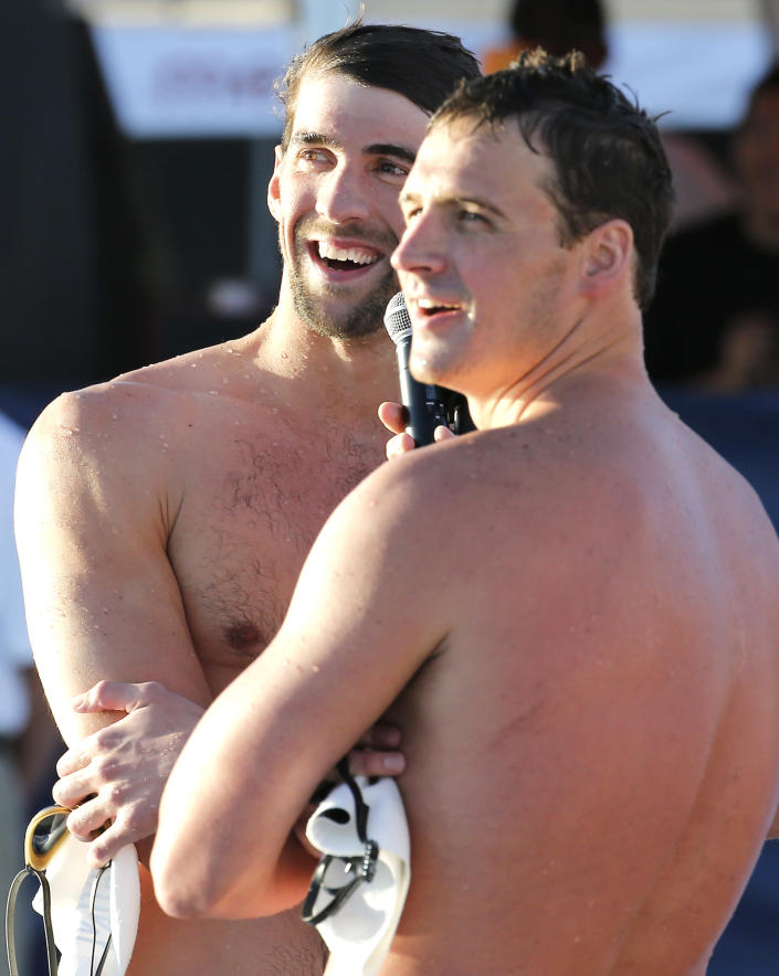 Michael Phelps, left, and Ryan Lochte look toward the crowd after competing in the 100-meter butterfly final during the Arena Grand Prix, Thursday, April 24, 2014, in Mesa, Ariz. Phelps was competing for the first time since the 2012 London Olympics. Lochte finished first and Phelps finished second in the final. (AP Photo/Matt York)