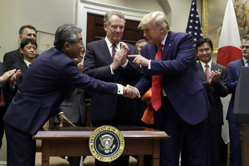 President Donald Trump points to Japanese Ambassador to the United States Shinsuke Sugiyama, left, as U.S. Trade Representative Robert Lighthizer, center, watches at the end of a signing ceremony for a trade agreement with Japan in the Roosevelt Room of the White House, Monday, Oct. 7, 2019, in Washington. (AP Photo/Evan Vucci)