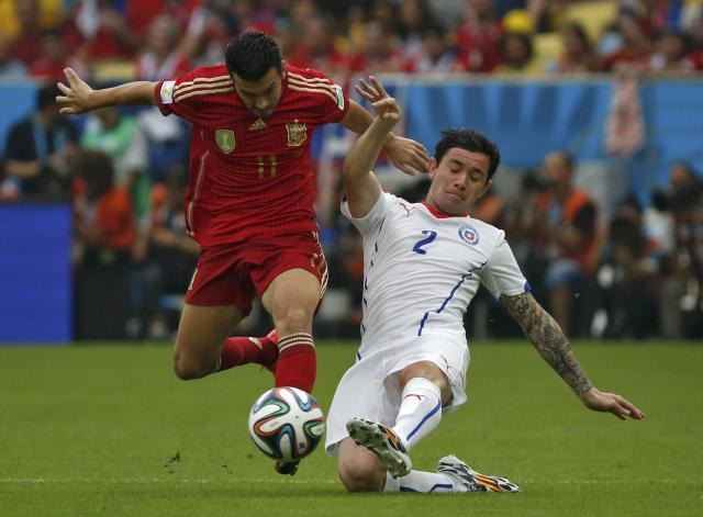 Spain's Rodriguez and Chile's Mena fight for the ball during their 2014 World Cup Group B soccer match at the Maracana stadium in Rio de Janeiro