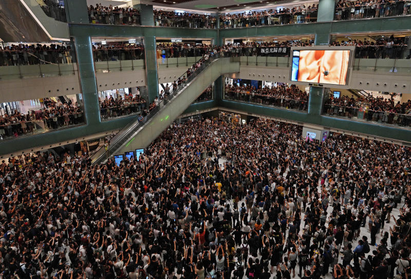 """Local residents sing a theme song written by protesters """"Glory be to thee"""" at a shopping mall in Hong Kong Wednesday, Sept. 11, 2019. Hong Kong Chief Executive Carrie Lam reassured foreign investors Wednesday that the Asian financial hub can rebound from months of protests, despite no sign that the unrest will subside. (AP Photo/Vincent Yu)"""