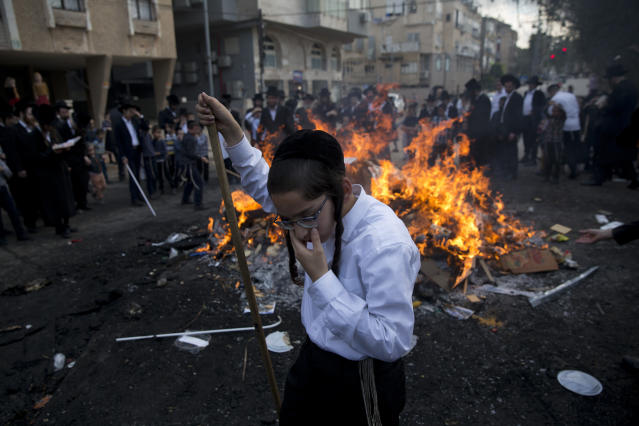 Ultra-Orthodox Jewish men and children burn leavened items in final preparation for the Passover holiday in the ultra-Orthodox Jewish town of Bnei Brak, Israel, Friday, April 19, 2019. Jews are forbidden to eat leavened foodstuffs during the Passover holiday that celebrates the biblical story of the Israelites' escape from slavery and exodus from Egypt. (AP Photo/Oded Balilty)