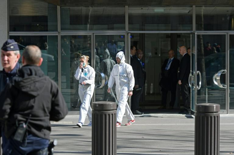 French forensic officers leave the IMF offices in Paris, after a parcel bomb exploded inside the building on March 16, 2017