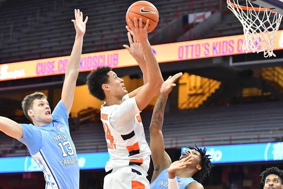 Syracuse Orange center Jesse Edwards (14) shoots near the basket as North Carolina Tar Heels forward Walker Kessler (13) and guard Caleb Love (bottom) defend in the first half at the Carrier Dome.