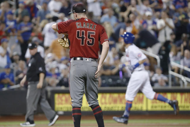 New York Mets' Todd Frazier, right, runs past Arizona Diamondbacks starting pitcher Taylor Clarke (45) after hitting a solo home run during the third inning of a baseball game Wednesday, Sept. 11, 2019, in New York. It was Frazier's second home run of the night. (AP Photo/Kathy Willens)