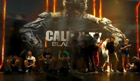 "Visitors queue to play the video game ""Call Of Duty: Black Ops III"" during the Gamescom fair in Cologne"
