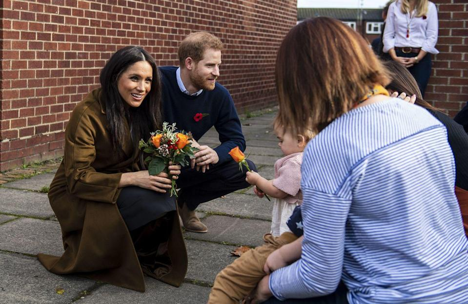 <p>During an intimate meeting with military families in Windsor, Meghan wore a rich brown-colored coat over a white blouse and black skirt.</p>