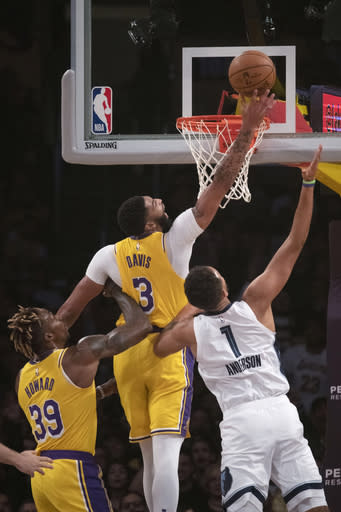 Los Angeles Lakers forward Anthony Davis, center, tips the ball to score over Memphis Grizzlies forward Kyle Anderson, right, during the first half of an NBA basketball game in Los Angeles, Tuesday, Oct. 29, 2019. (AP Photo/Kyusung Gong)