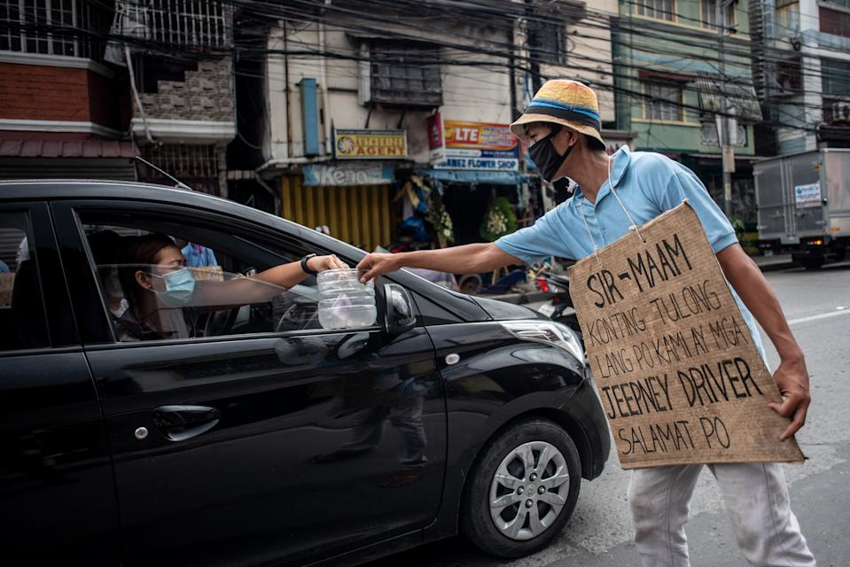 """A jeepney driver wearing a face mask and a placard reading """"sir/mam, asking for help, we are jeepney drivers"""" receives alms from a motorist on a road in Manila on August 6, 2020. (Photo: LISA MARIE DAVID/AFP via Getty Images)"""