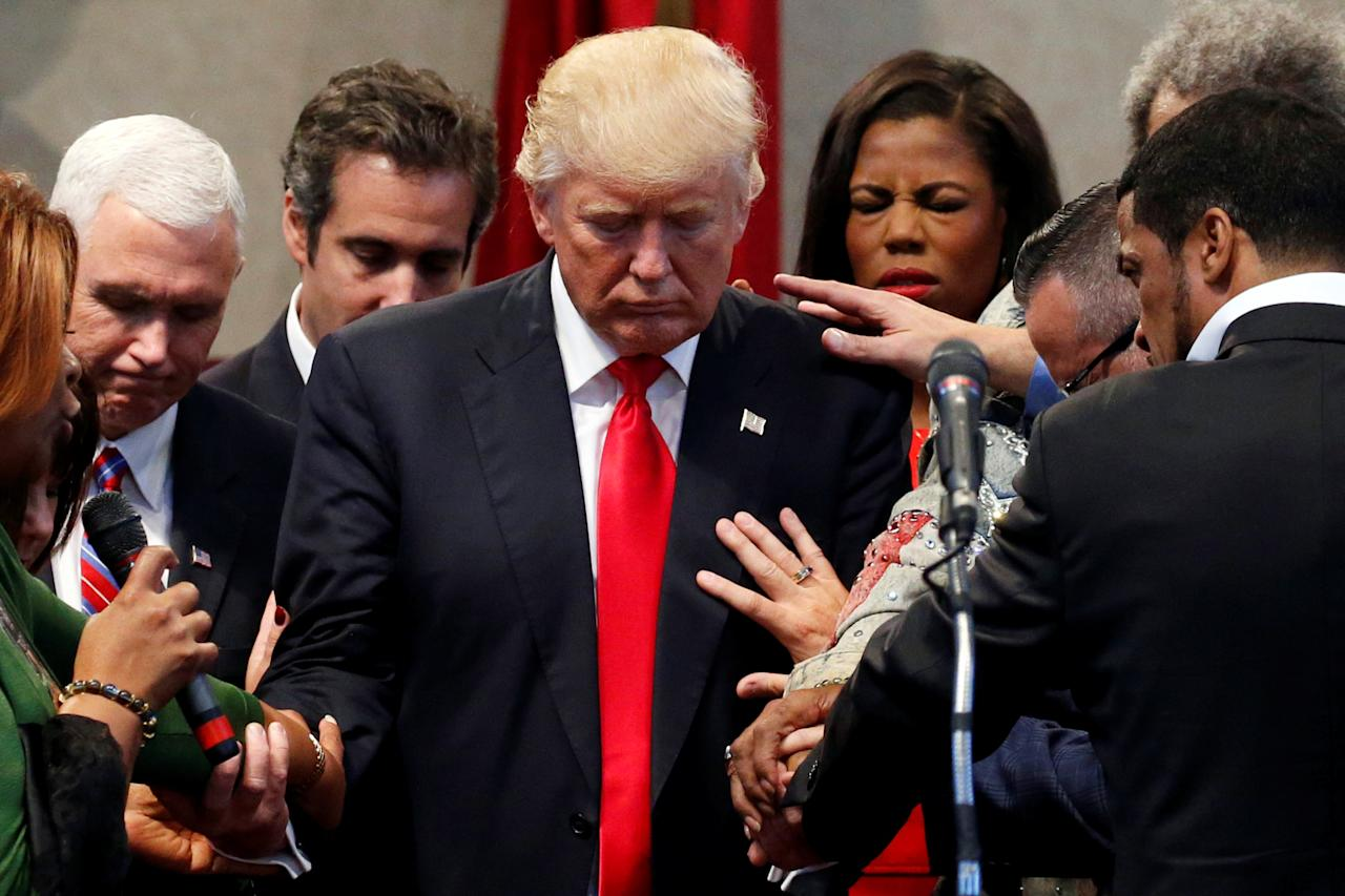 Members of the clergy lay hands and pray over Republican presidential nominee Donald Trump at the New Spirit Revival Center in Cleveland Heights, Ohio, U.S., September 21, 2016. REUTERS/Jonathan Ernst     TPX IMAGES OF THE DAY