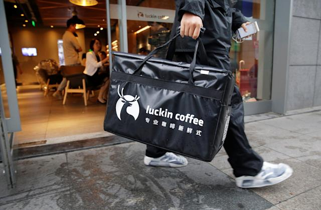 A deliveryman leaves a Luckin Coffee store with a takeout box for online sales in Beijing, China July 17, 2018. REUTERS/Jason Lee