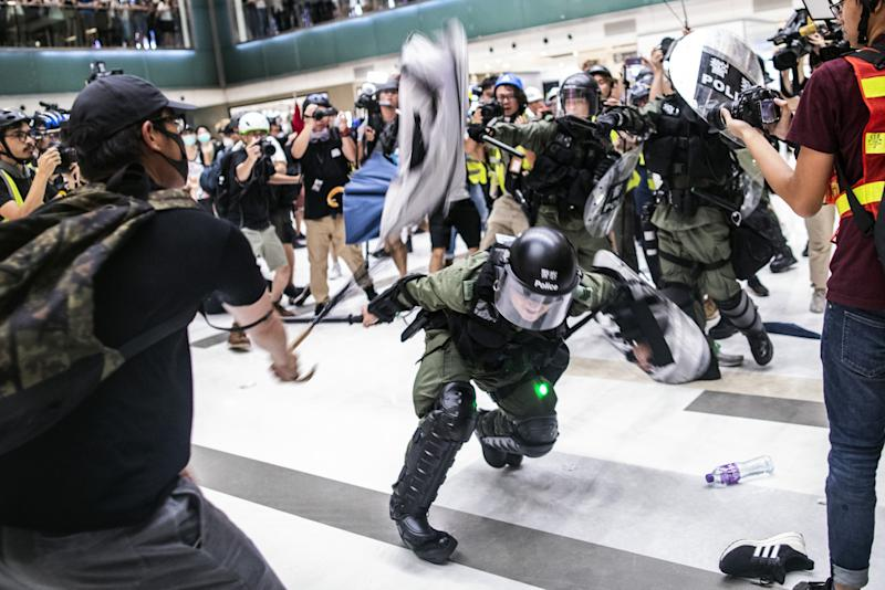 """(Bloomberg) -- Hong Kong police arrested more than 40 people after attempts to clear the remnants of a mass anti-government march resulted in dramatic clashes with demonstrators inside a suburban shopping mall, piling more pressure on embattled leader Carrie Lam.Scuffles broke out in New Town Plaza as police moved to clear stragglers from a rally earlier Sunday in Sha Tin, a popular destination for locals and visitors from China and home to one of the city's horse racing tracks. Rally organizers said 110,000 people had turned out to protest the city's chief executive and her controversial bid to allow extraditions to the mainland, while police estimated the crowd at 28,000.The unrest came as the Financial Times reported that Lam had offered to resign in recent weeks, only to be refused by authorities in China, citing unidentified people familiar with the matter. Beijing insisted that she remain in office to fix """"the mess she created,"""" according to one person.Lam on Monday vowed she would continue in her position as Hong Kong's leader.""""The chief executive's tenure is five years. Although I face a lot of difficulties, I have repeatedly said publicly that I still have the responsibility and enthusiasm to continue my work during my tenure,"""" she told reporters at a hospital after visiting officers injured in the clashes.New MessageCrowds of Hong Kong protesters have turned out in unprecedented sizes every week since mid-June. In recent days their ire has focused on China, which has ruled the former British colony since 1997. Thousands of demonstrators last Sunday walked through the Tsim Sha Tsui area popular with mainland tourists toward the city's new high-speed rail station to China.Beijing has continued to back Lam publicly. Chinese Foreign Ministry spokesman Geng Shuang said Monday that he hadn't heard anything about the FT's report and that the central government """"firmly supports"""" her leadership. Sunday's protesters threw objects including umbrellas, water bottles a"""